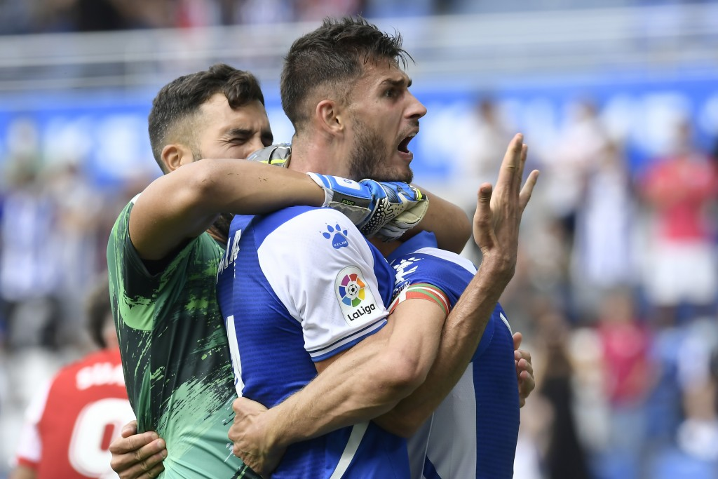 Alaves players celebrate after defeating Atletico Madrid at the end of a Spanish La Liga soccer match at the Mendizorroza stadium in Vitoria, Spain, S...