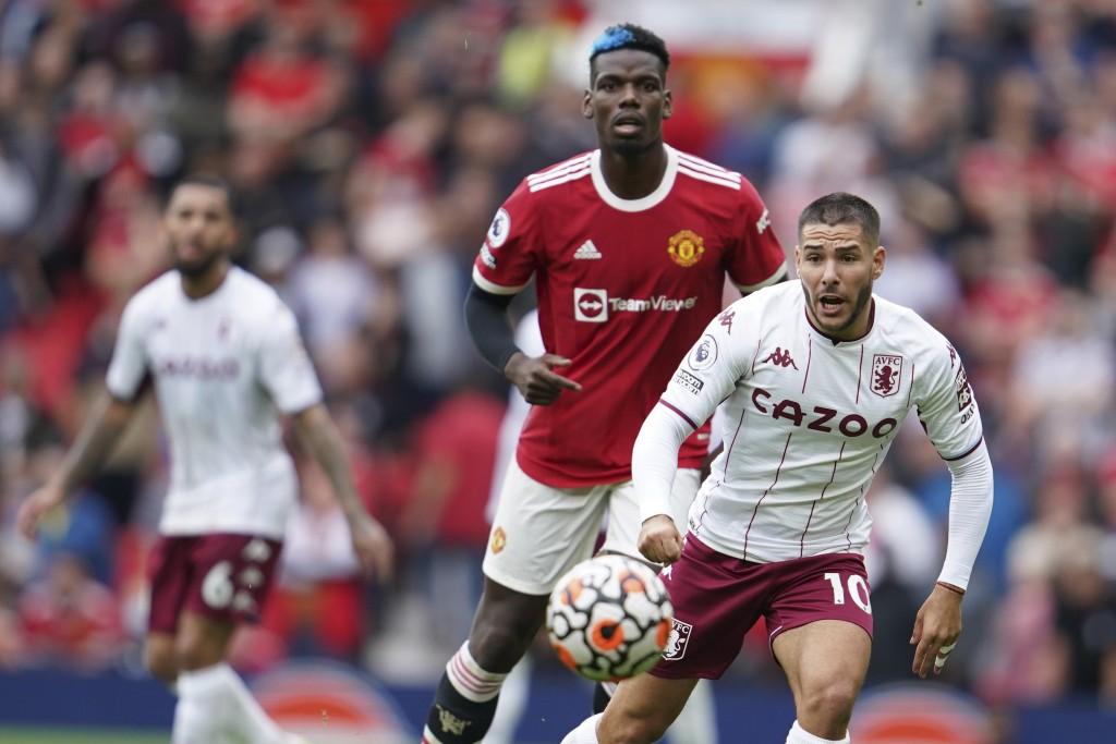Aston Villa's Emiliano Buendia is challenged by Manchester United's Paul Pogba, rear, during the English Premier League soccer match between Mancheste...