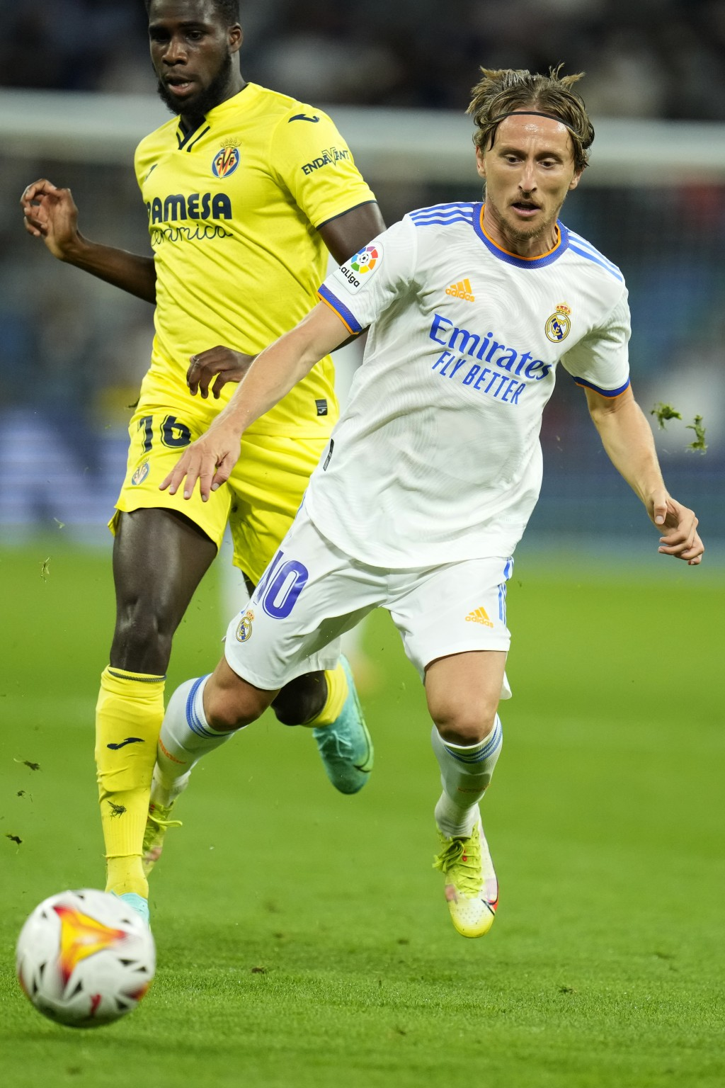 Real Madrid's Luka Modric falls as he is challenged by Villarreal's Boulaye Dia during a Spanish La Liga soccer match between Real Madrid and Villarre...