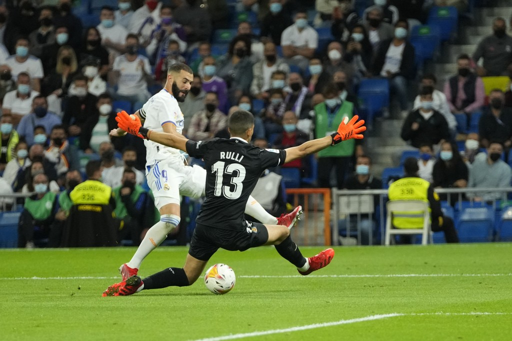 Real Madrid's Karim Benzema attempts a shot on goal past Villarreal's goalkeeper Geronimo Rulli during a Spanish La Liga soccer match between Real Mad...