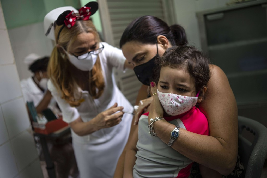 A mother holds her daughter who is injected with a dose of the Soberana-02 COVID-19 vaccine, in Havana, Cuba, Thursday, Sept. 16, 2021. Cuba began ino...