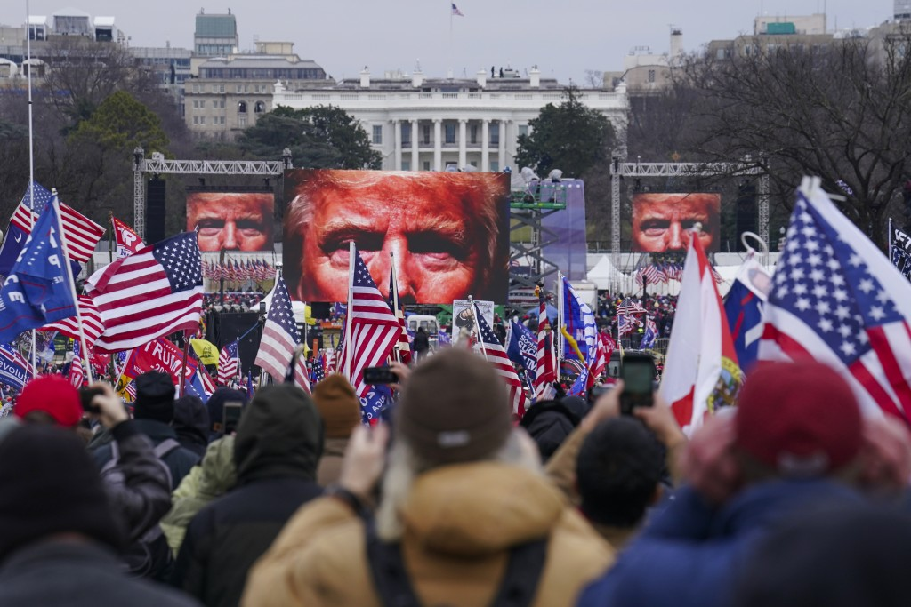 FILE - In this Jan. 6, 2021, file photo, the face of President Donald Trump appears on large screens as supporters participate in a rally in Washingto...