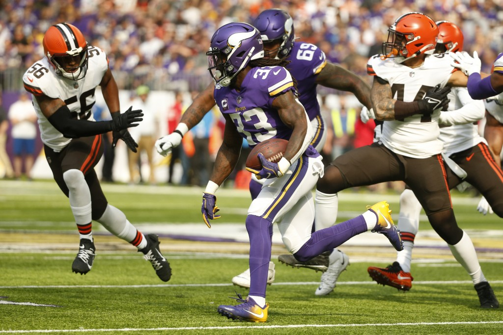 Minnesota Vikings running back Dalvin Cook (33) runs from Cleveland Browns middle linebacker Malcolm Smith (56) during the first half of an NFL footba...