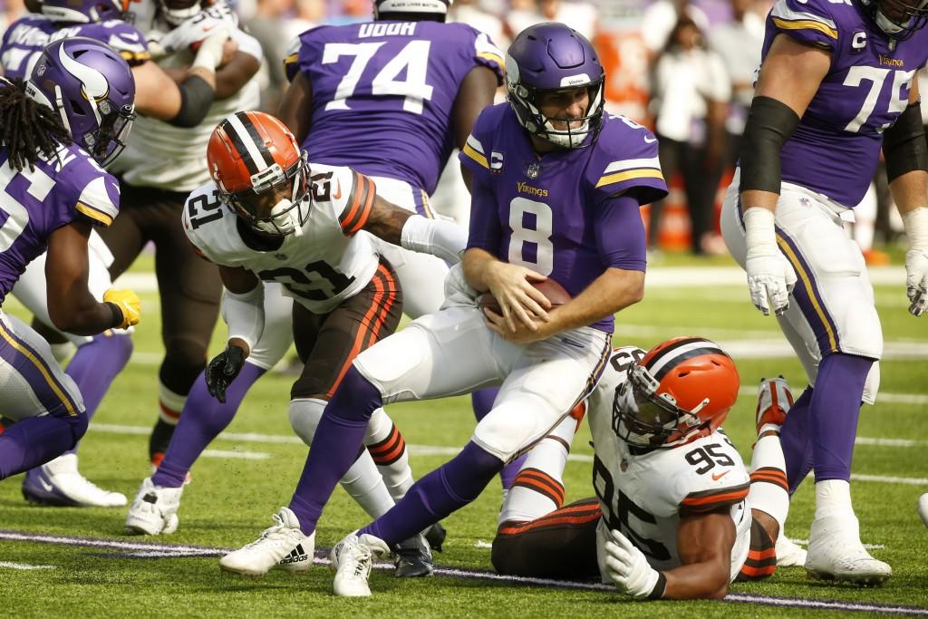 Minnesota Vikings quarterback Kirk Cousins (8) is sacked by Cleveland Browns cornerback Denzel Ward (21) and defensive end Myles Garrett (95) during t...