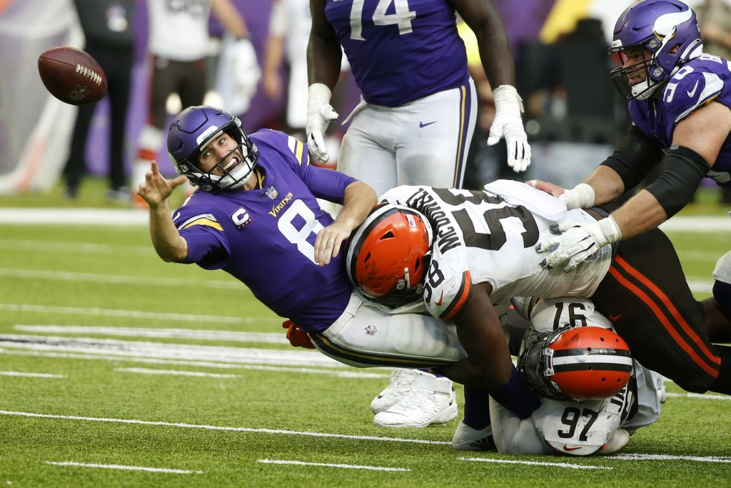 Minnesota Vikings quarterback Kirk Cousins (8) passes as he is tackled by Cleveland Browns defensive tackle Malik Jackson (97) and defensive tackle Ma...