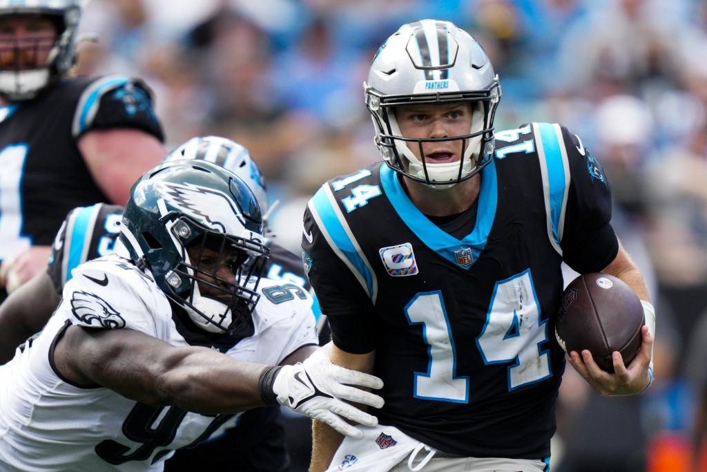 Carolina Panthers quarterback Sam Darnold breaks away from Philadelphia Eagles defensive tackle Javon Hargrave during the second half of an NFL footba...
