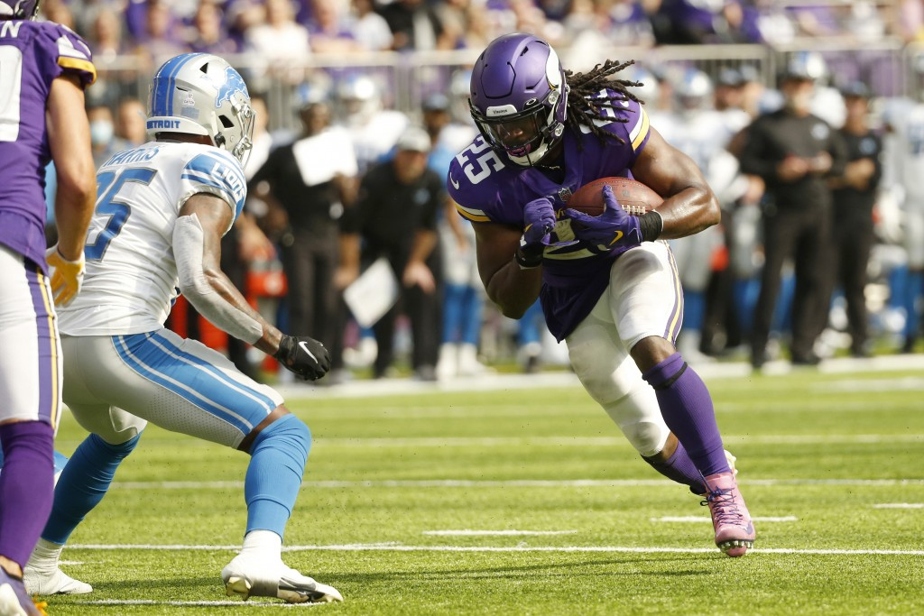 Minnesota Vikings running back Alexander Mattison runs from Detroit Lions safety Will Harris, left, during a 15-yard touchdown reception during the fi...
