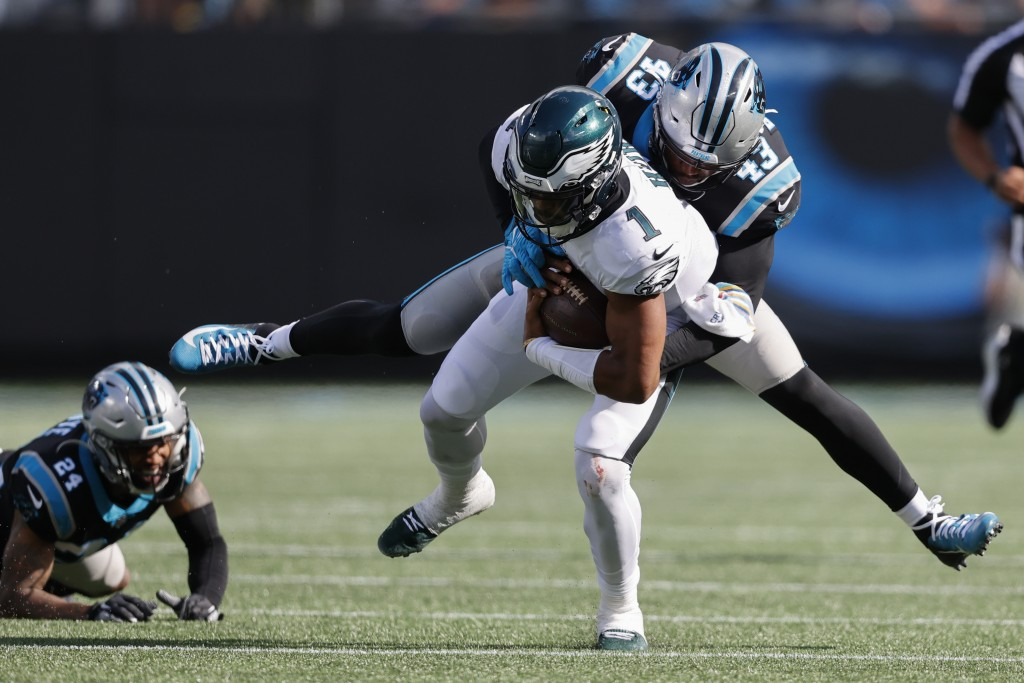 Philadelphia Eagles quarterback Jalen Hurts is tackled by Carolina Panthers outside linebacker Haason Reddick during the second half of an NFL footbal...