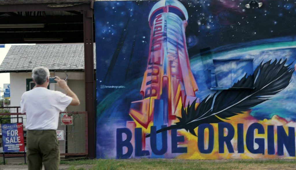 Gene Walker, of Denison, Texas, makes a photo of a Blue Origin mural on a building for sale in Van Horn, Texas, Tuesday Oct. 12, 2021. Today's launch ...