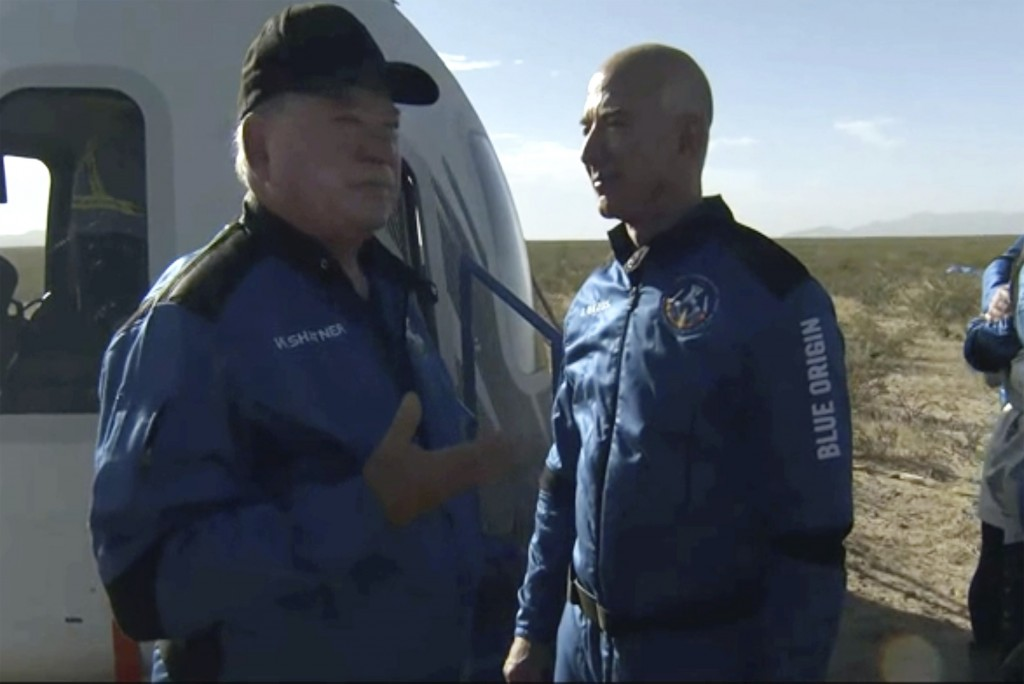 In this image provided by Blue Origin, William Shatner talks with Jeff Bezos about his experience after exiting the Blue Origin capsule near Van Horn,...