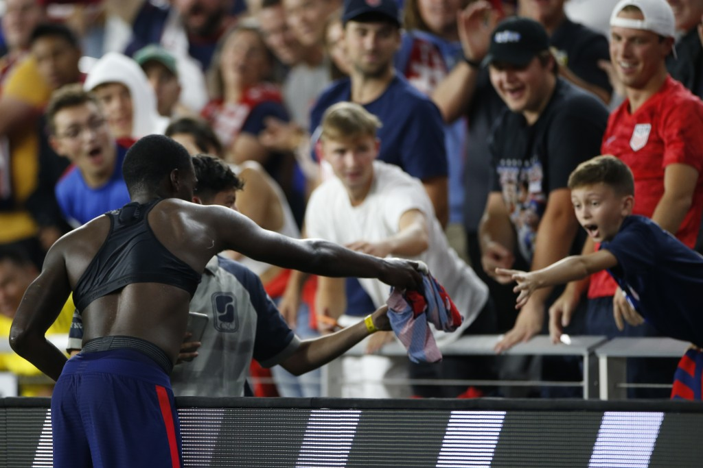 United States' Tim Weah, left, gives his jersey to a fan as he leaves the World Cup qualifying soccer match against Costa Rica during the second half ...