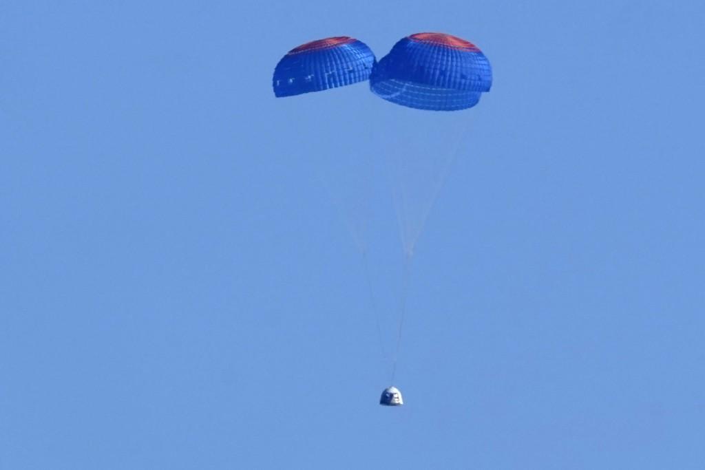 Parachutes slow the descent of the Blue Origin capsule with passengers William Shatner, Chris Boshuizen, Audrey Powers and Glen de Vries near the comp...
