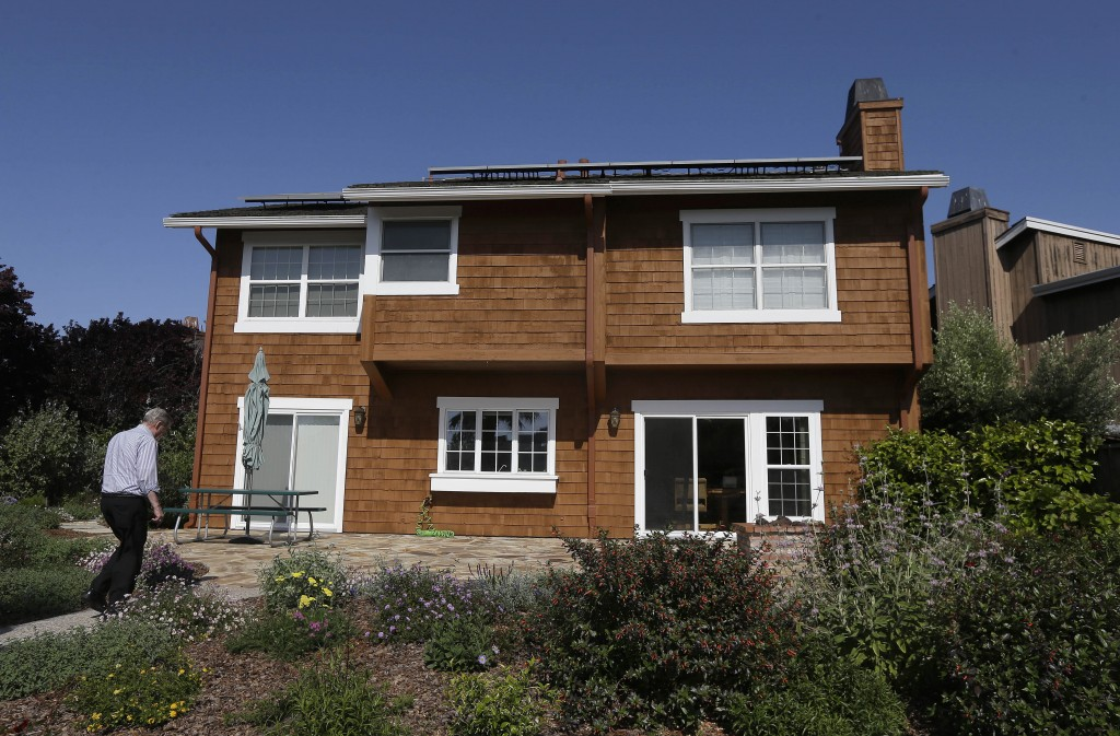 FILE - David Cunningham walks toward his solar panel-topped home, on April 20, 2015, in Foster City, Calif. With prices surging worldwide for heating ...
