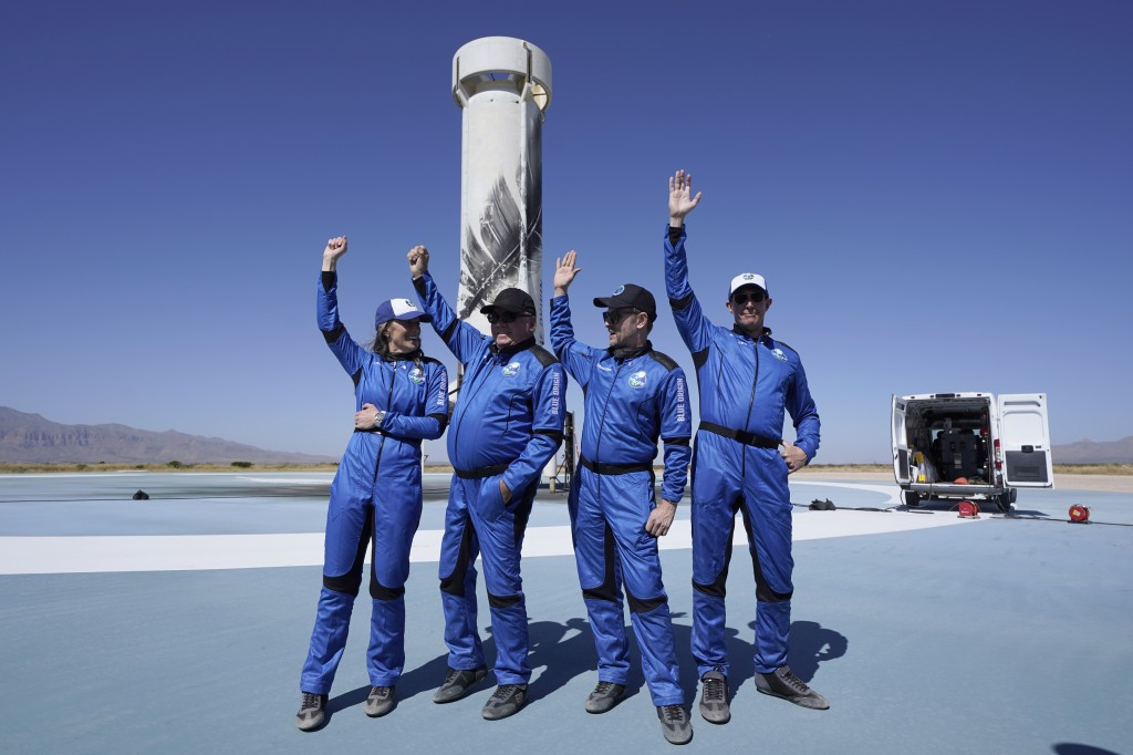 Blue Origin's New Shepard rocket latest space passengers from left, Audrey Powers, William Shatner, Chris Boshuizen, and Glen de Vries raise their han...