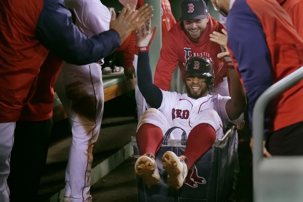 FILE - In this May 4, 2021, file photo, Boston Red Sox's Xander Bogaerts high-fives teammates while being pushed in a laundry cart through the dugout ...