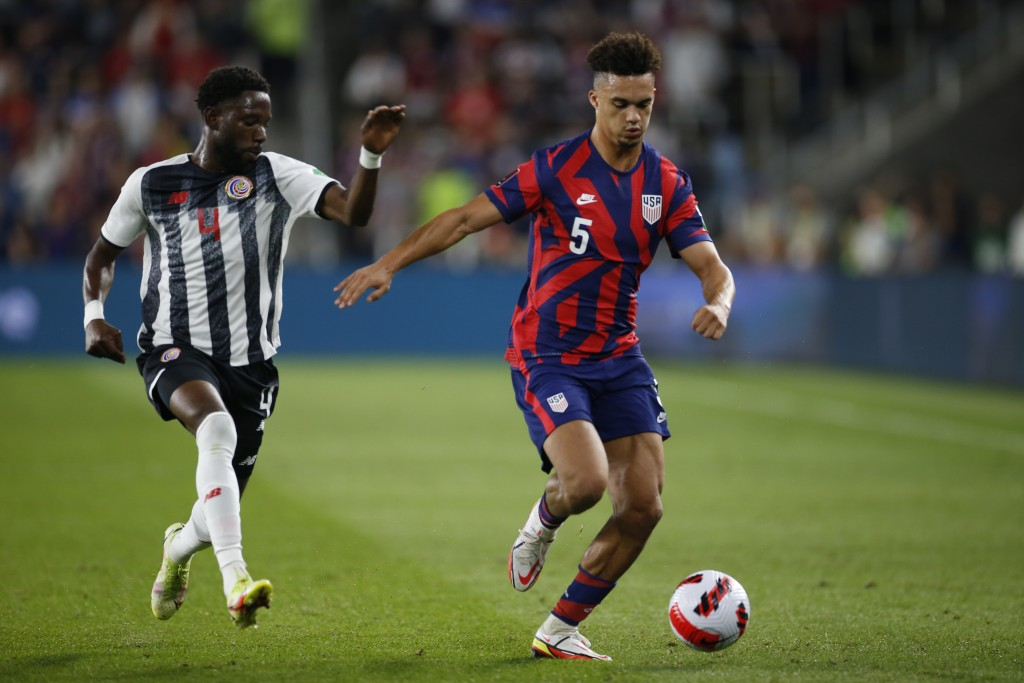 Costa Rica's Keysher Fuller, left, chases United States' Antonee Robinson up the field during the first half of a World Cup qualifying soccer match We...