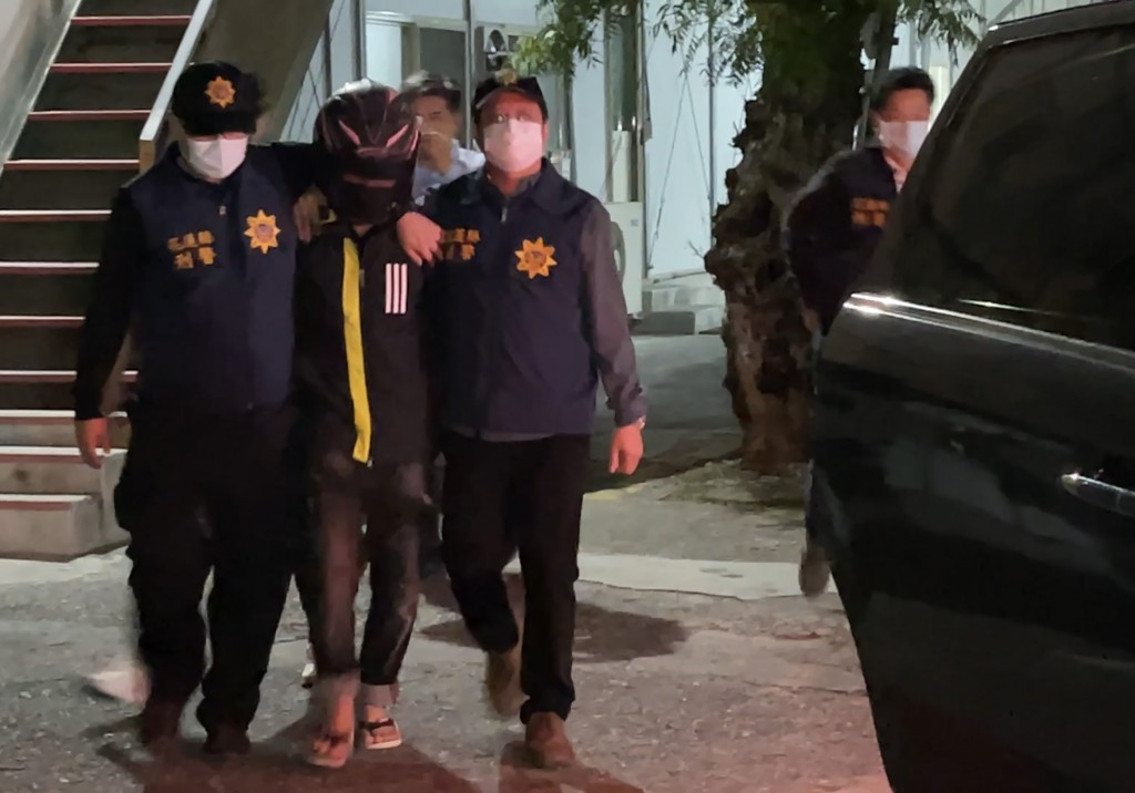 Hua Hsin-hao (second from left) is escorted by police.