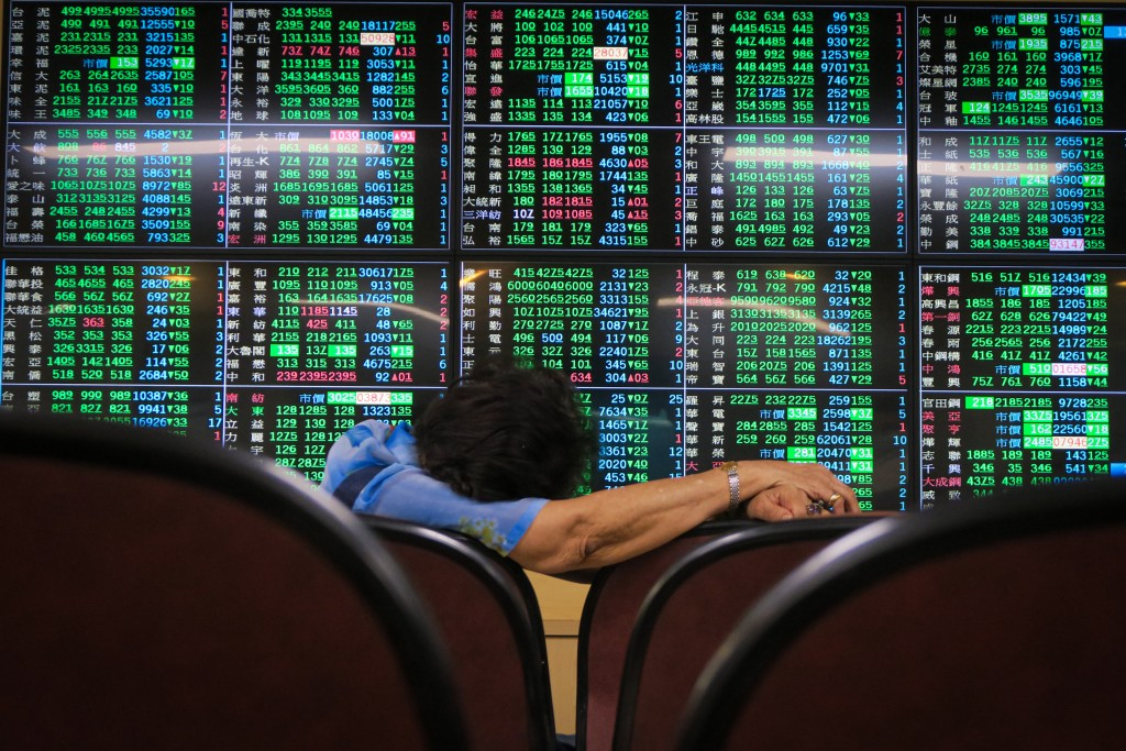 Woman looks disheartened as stocks plunge on Taiwan Stock Exchange.