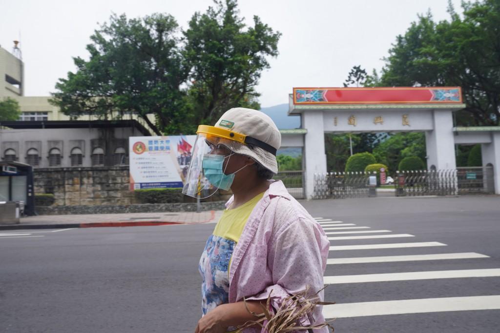 民眾外出戴上防護面罩與口罩加強防疫。(來源:中央社)