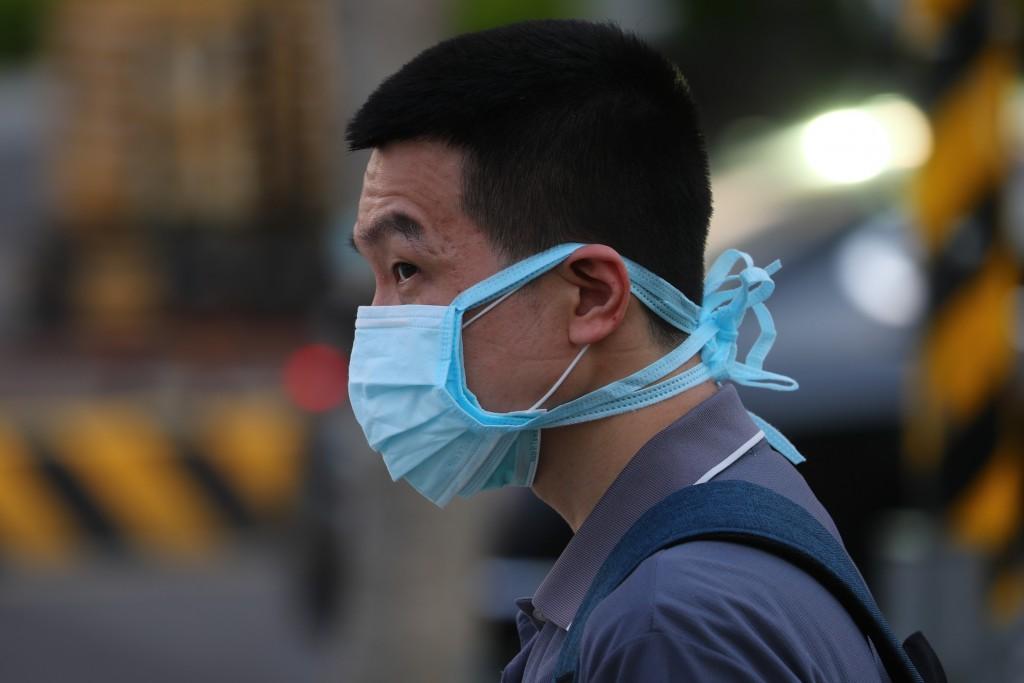 武漢肺炎(2019冠狀病毒疾病,COVID-19)本土疫情嚴 峻,26日街頭有民眾一次戴3層口罩加強防疫。