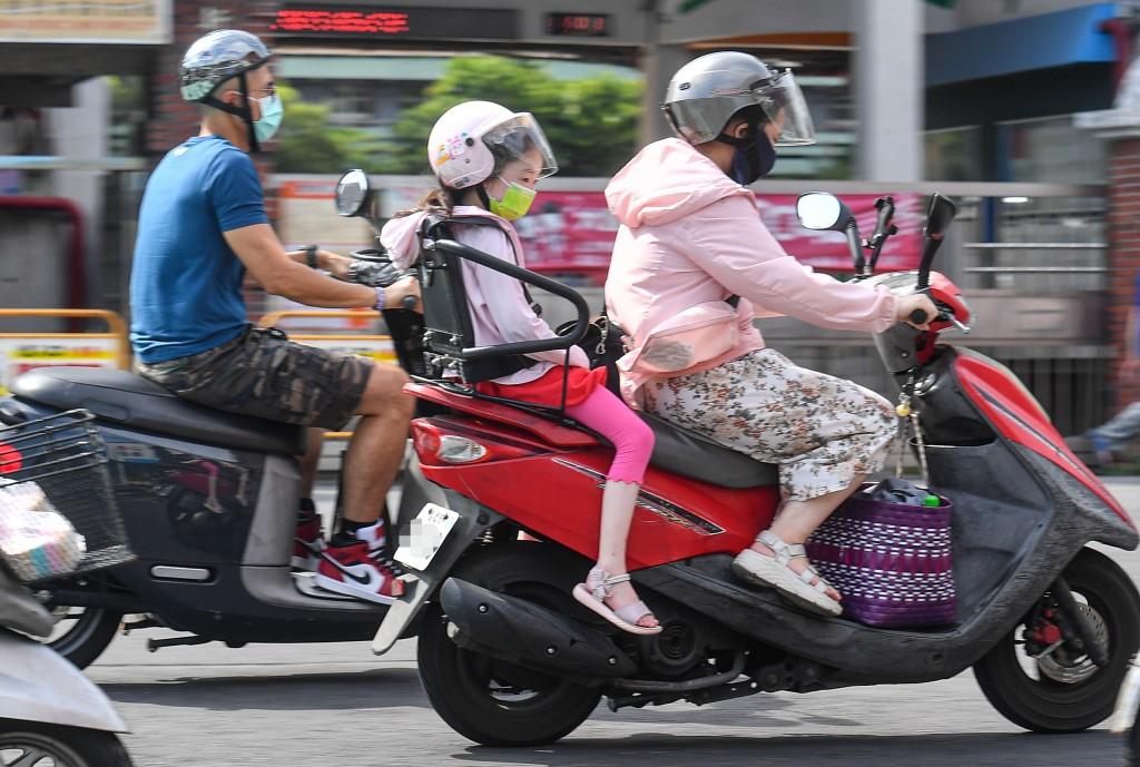 圖為28日午後有家長騎車載著孩子通勤。