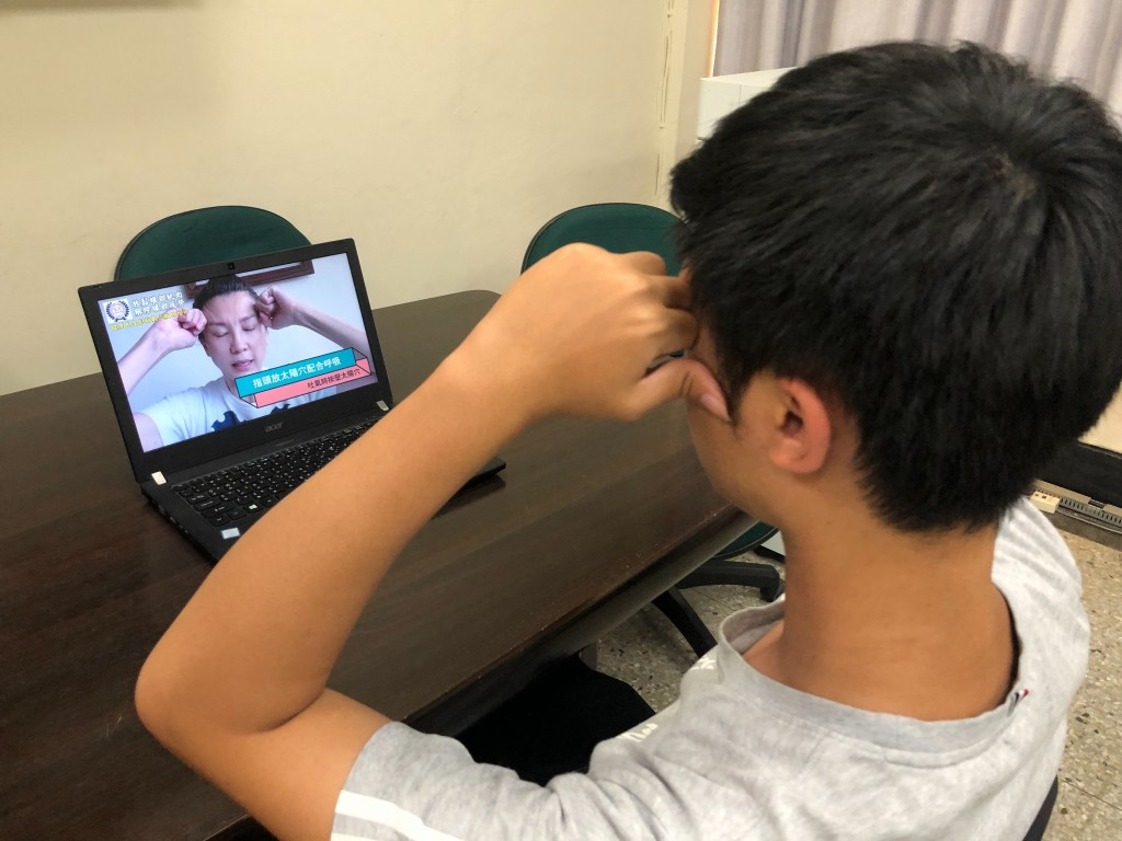 A cosmeticsinstructor delivers an online lesson to a male student.