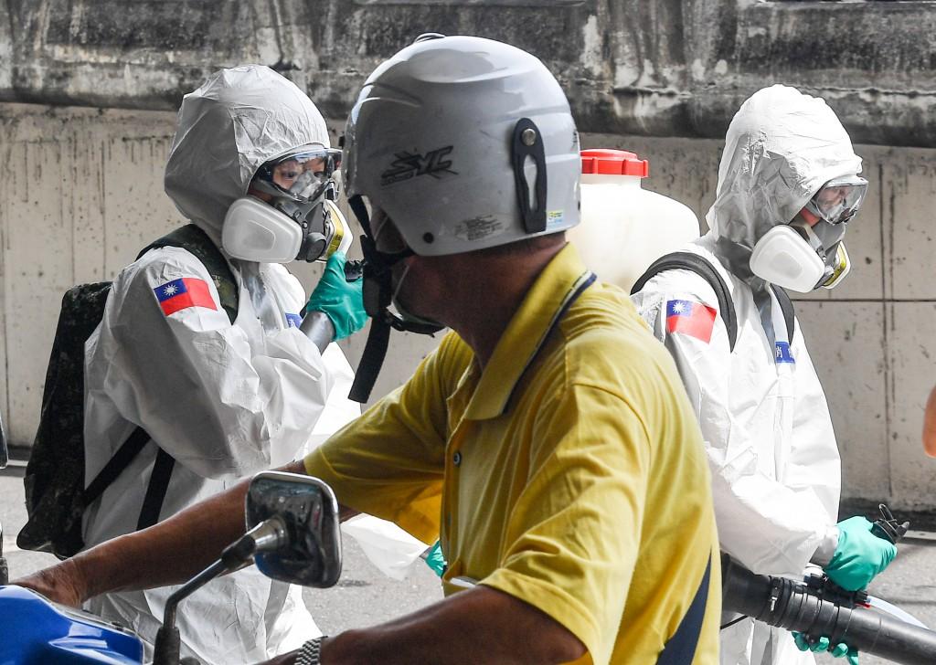 COVID-19疫情延燒,國軍化學兵2日上午前往台北市西 寧市場,以人力噴灑的方式沿途消毒,與通勤民眾錯身 而過。 中央社記者鄭清元攝 1...