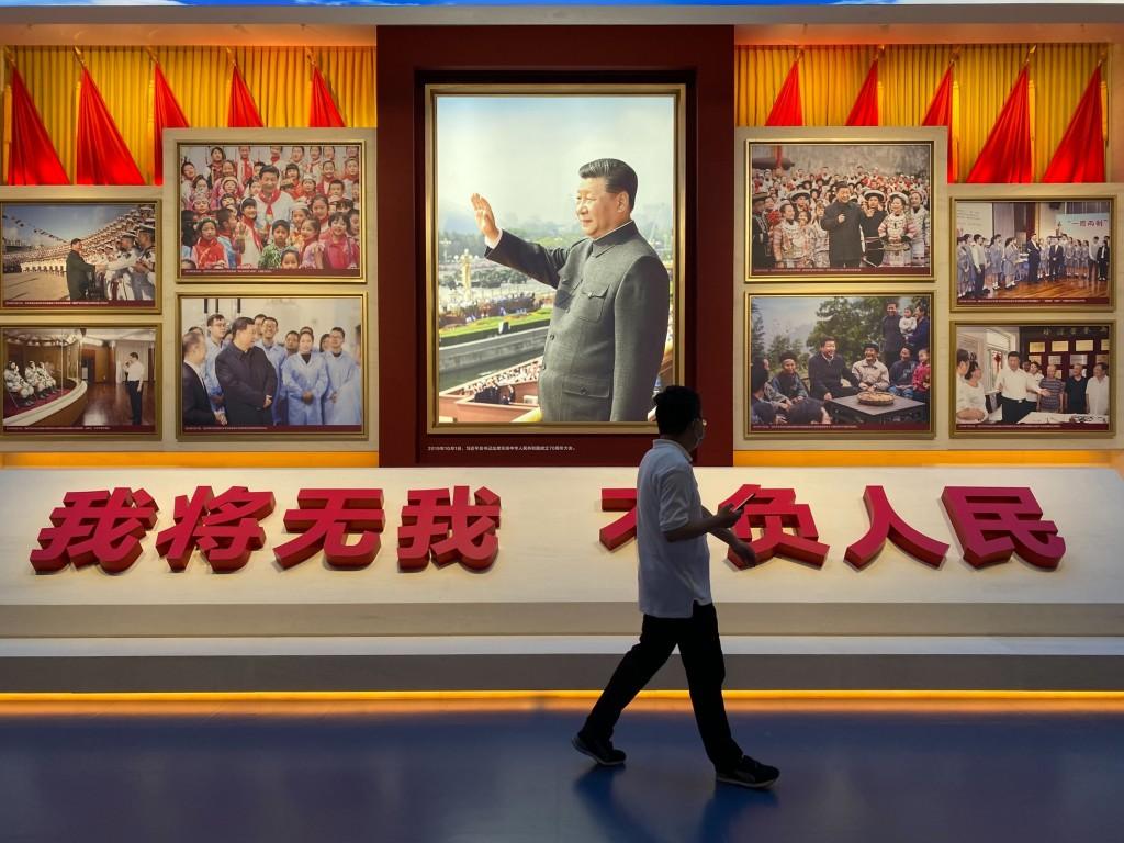 圖為中共黨史展覽館陳設,一名民眾經過中共總書記習近平肖象。