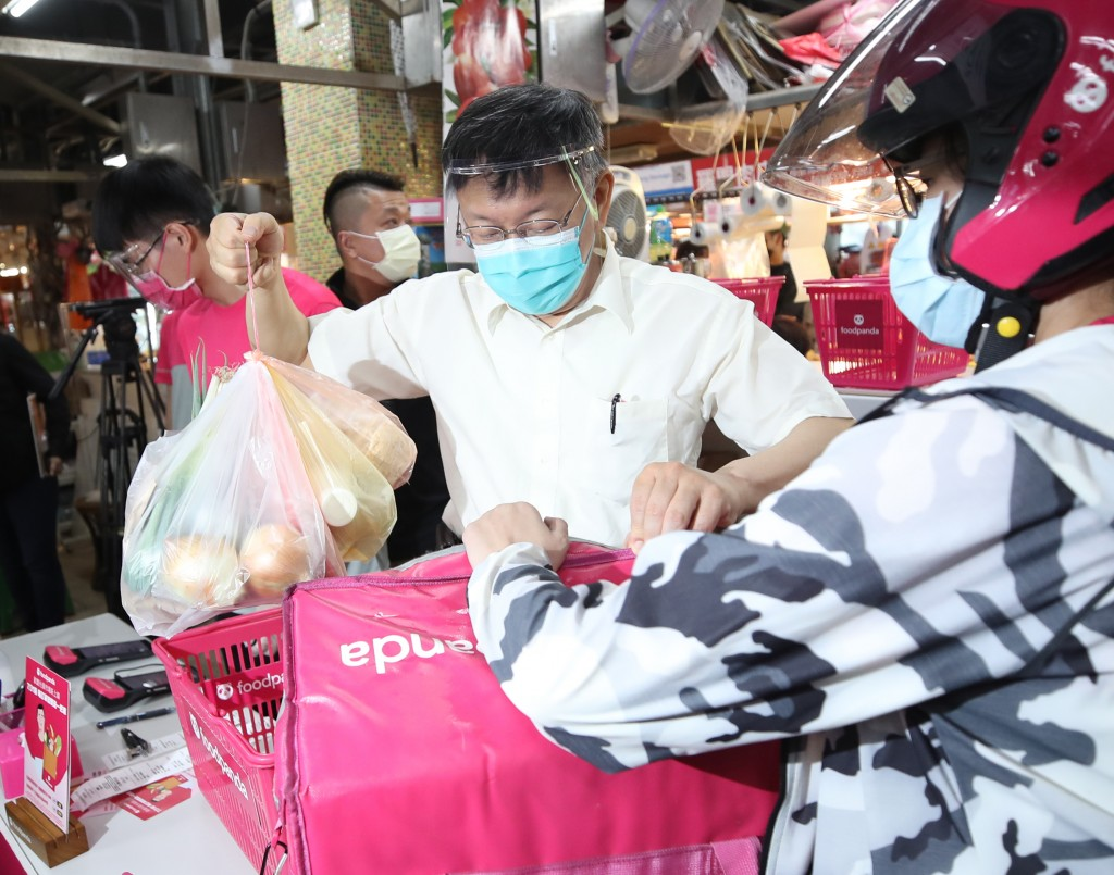 Mayor Ko prepares goods at a traditional market in Taipei.