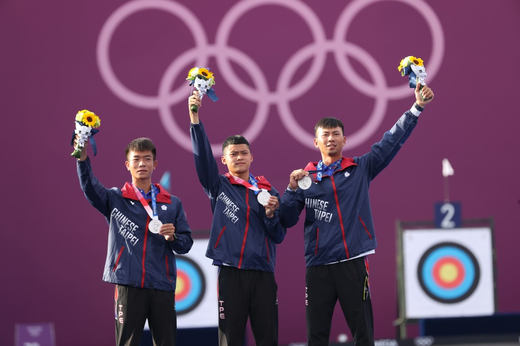 Taiwan men's archery team members hold up silver medals.