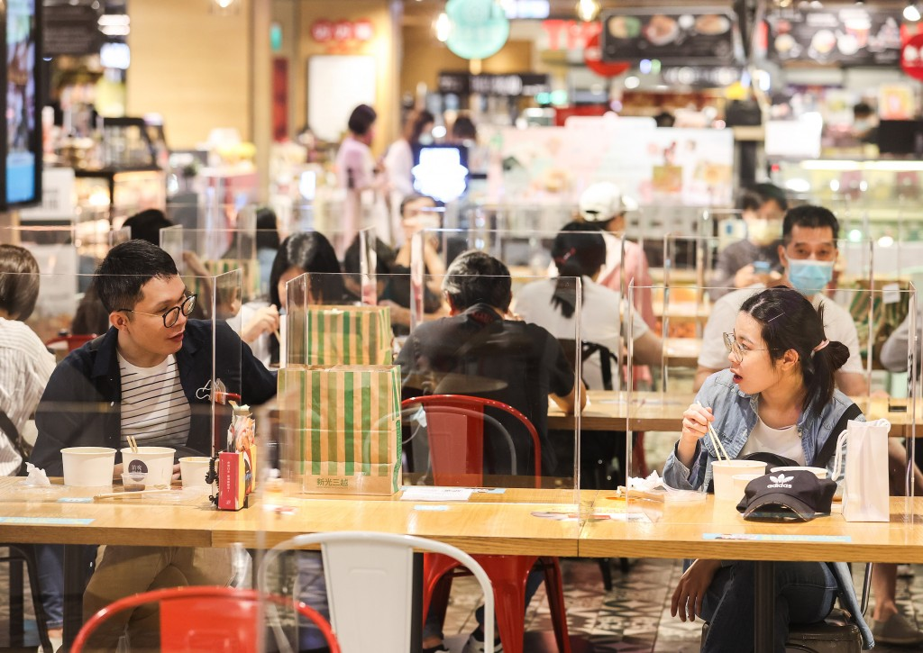 Two diners conversing while separated by a partition and empty seat in Taipei City.