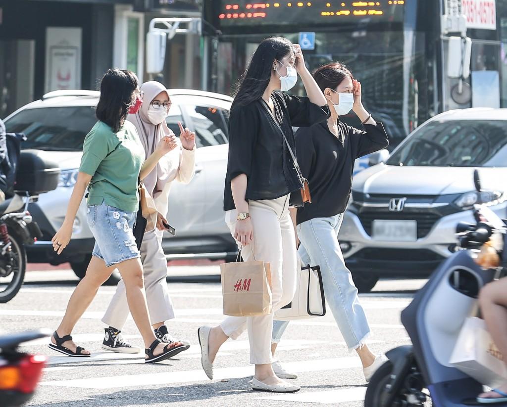 台北市區天氣晴朗炎熱,民眾在街頭以手遮擋豔陽。