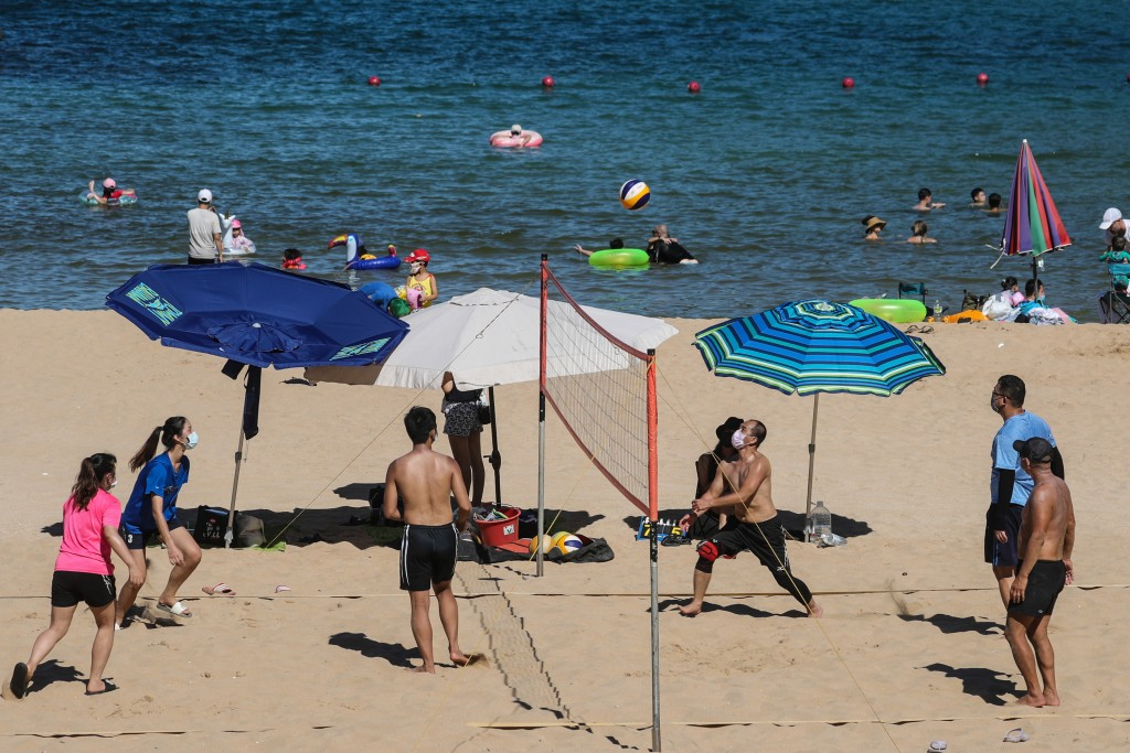 People wearing masks as they play volleyball at Waimushan Seaside Scenic Area.