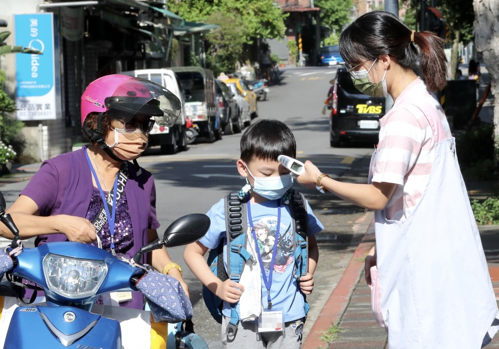 Teacher takes student's temperature outside school in Taipei on Sept. 13.