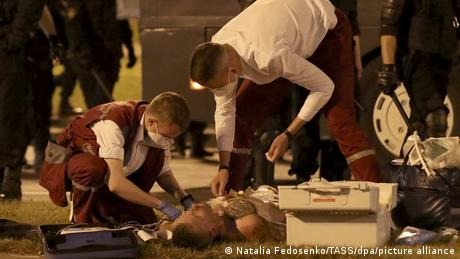 Medics help an injured man during the protest in Belarus on August 9, 2020