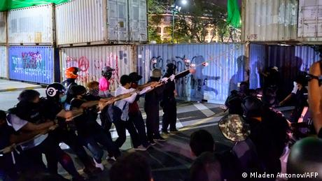 Protesters pull down a shipping container set up to block access to the nearby Grand Palace on March 20, 2021