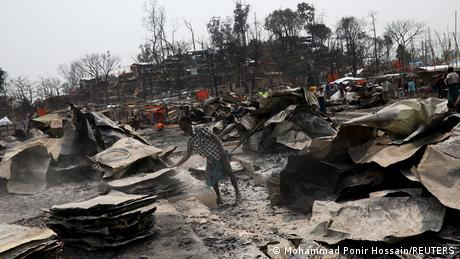 A Rohingya refugee stands among the remains of burnt materials after a fire broke out recently at a camp in Cox's Bazar