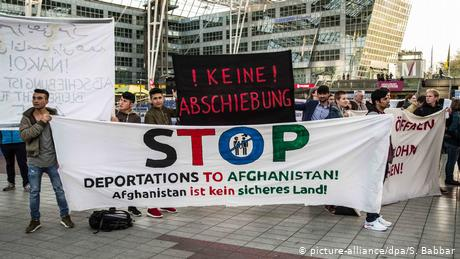 Protesters hold up anti-deportation signs at Munich's international airport