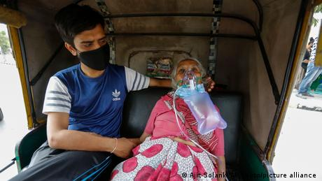 A COVID-19 patient wearing oxygen mask waits inside an auto rickshaw outside a government hospital in Ahmedabad