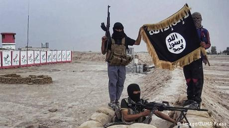 IS fighters in Syria hold up the terror group's flag in August 2015