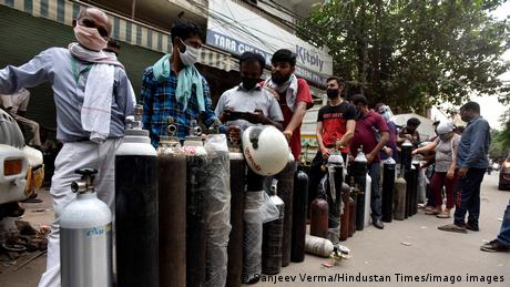 People line up to get oxygen cylinders filled as India grapples with the world's worst coronavirus outbreak.