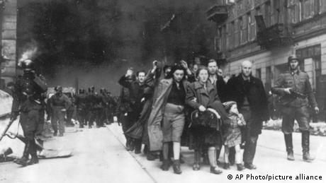 Polish Jews are led away for deportation by German SS soldiers during the destruction of the Warsaw Ghetto in 1943