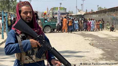 A Taliban fighter stands guard at the border with Pakistan