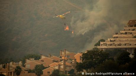 A helicopter makes a water drop over a wildfire near Estepona, Spain