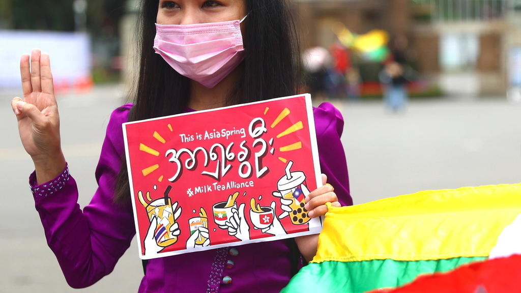 A woman shows the three-finger salute and holds up a poster against Myanmar military coup as part of the Milk Tea Alliance united rally in Taipei, Tai...