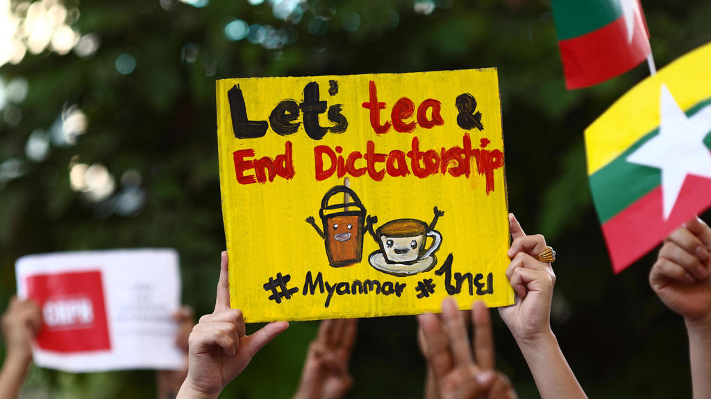 """Myanmar migrants in Thailand hold """"Milk Tea Alliance"""" signs at a Bangkok protest on February 28, 2021."""