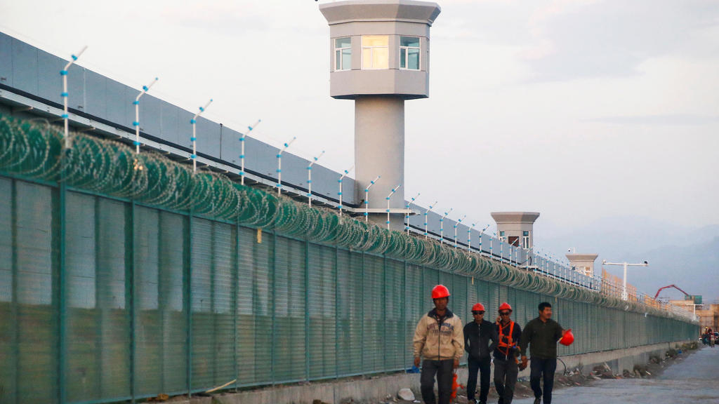 FILE PHOTO: Workers walk by the perimeter fence of what is officially known as a vocational skills education centre in Dabancheng in Xinjiang Uighur A...