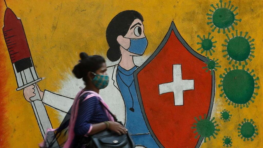 印度疫情嚴峻,民眾全副武裝走過孟買街頭。(France24圖片)