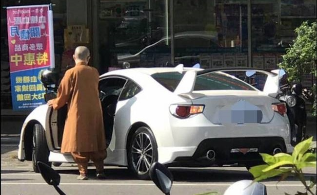 Buddhist nun entering her modified Toyota 86 sports car