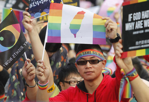 A same-sex marriage supporter holds a rainbow flag with Taiwan map during rally in Taipei.